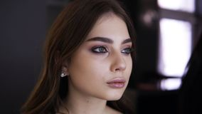 O retrato de uma moça bonita com luz compõe e por muito tempo o cabelo justo em compõe o estúdio Correção de Visagist filme