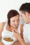 O retrato de uma mulher alimentou com cereal por seu homem Imagem de Stock