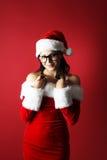 O retrato de uma mulher bonita que torce seu cabelo em torno de seus dedos que vestem Papai Noel veste-se Imagens de Stock Royalty Free