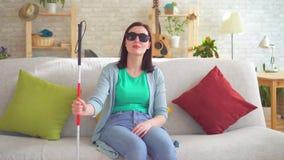 O retrato de uma mulher cega nova desabilitou com um bastão para as cortinas video estoque
