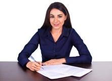 O retrato de uma mulher de negócio alegre que senta-se em sua mesa Adan assina acima o contrato no fundo branco Imagem de Stock