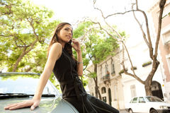 Mulher de negócios que inclina-se no carro com telefone. fotografia de stock