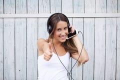 O retrato de uma mulher feliz escuta música com polegares acima Imagem de Stock