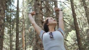 O retrato de uma mulher feliz na floresta, menina aprecia a madeira, turista com a trouxa no parque nacional, estilo de vida do c Foto de Stock