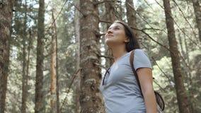 O retrato de uma mulher feliz na floresta, menina aprecia a madeira, turista com a trouxa no parque nacional, estilo de vida do c Fotos de Stock Royalty Free