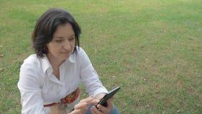 O retrato de uma mulher de meia idade que descansa em um esclarecimento, e lê mensagens em seu telefone celular video estoque
