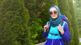 O retrato de uma mulher muçulmana bonita no turista do hijab com uma trouxa nos vidros usa a fala e o sorriso filme