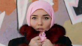O retrato de uma mulher muçulmana com um lenço cobriu a cabeça em um fundo da parede vídeos de arquivo