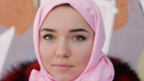 O retrato de uma mulher muçulmana com um lenço cobriu a cabeça em um fundo da parede video estoque