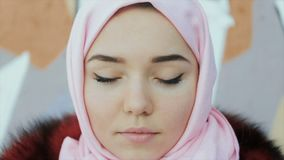 O retrato de uma mulher muçulmana com um lenço cobriu a cabeça em um fundo da parede filme