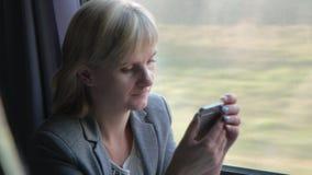 O retrato de uma mulher de negócio com um smartphone, senta-se pela janela no trem Em um conceito da viagem do curso filme
