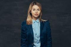 O retrato de uma mulher de negócio loura sensual vestiu-se em um terno formal e em uma camisa azul, levantando em um estúdio Na fotos de stock