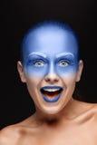 O retrato de uma mulher que levantasse cobriu com a pintura azul Fotografia de Stock Royalty Free