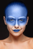 O retrato de uma mulher que levantasse cobriu com a pintura azul Imagens de Stock Royalty Free
