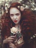 O retrato de uma mulher sensual nova bonita com cabelo encaracolado vermelho muito longo na mola floresce Cores da mola fotos de stock