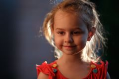 O retrato de uma parte externa louro encantador da posição da menina em uma noite morna do verão, o sol ilumina o cabelo de fotos de stock