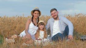O retrato do ar livre novo da família, pares felizes senta-se com sua filha pequena que sorri no piquenique na grão dourada do ou filme