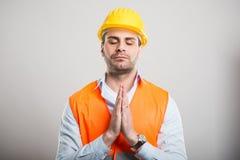 O retrato do arquiteto novo que guarda as mãos gosta junto de rezar foto de stock