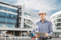 O retrato do arquiteto ou do chefe de máquinas novo usa a tabuleta digital no canteiro de obras Imagens de Stock Royalty Free