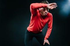 O retrato do atleta pensativo do homem do attractiva que relaxa depois que duro malha no gym, pôs sua mão sobre a cabeça Vestir d Fotografia de Stock