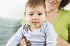 O retrato do bebê adorável que senta-se em sua mãe arma-se. imagem de stock