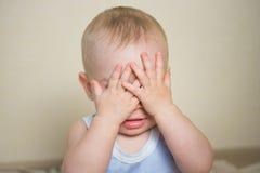 O retrato do bebê fechado seus olhos com as mãos a ser invisíveis ou não querendo ver, jogando o divertimento espreita uma vaia imagem de stock