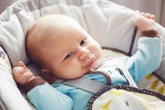 O retrato do bebê pequeno louro caucasiano branco engraçado adorável bonito recém-nascido com cinza azul eyes na roupa azul Imagem de Stock Royalty Free
