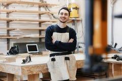 O retrato do carpinteiro na roupa de trabalho na frente da bancada Retrato do homem de sorriso no trabalho na oficina do carpinte imagem de stock royalty free