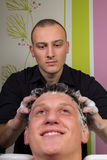 O retrato do cliente masculino que obtém seu cabelo lavou no salão de beleza imagem de stock royalty free