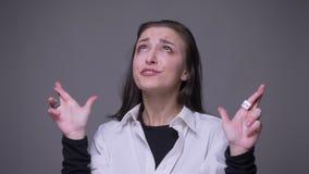 O retrato do close up da fêmea caucasiano atrativa adulta que tem seus dedos cruzou ser rezar ansioso e preocupado com vídeos de arquivo