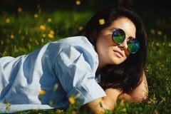 O retrato do close-up da jovem mulher que encontra-se entre a grama verde, óculos de sol redondos à moda vestindo, tem a expressã Fotografia de Stock