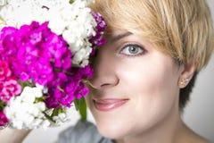 O retrato do close-up da mulher à moda bonita nova com mola lindo floresce As flores cobrem a metade da cara Fotos de Stock Royalty Free