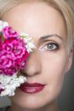 O retrato do close-up da mulher à moda bonita nova com mola lindo floresce As flores cobrem a metade da cara Foto de Stock