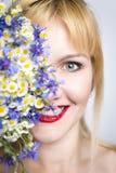 O retrato do close-up da mulher à moda bonita nova com mola lindo floresce As flores cobrem a metade da cara Fotografia de Stock