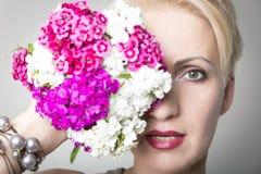 O retrato do close-up da mulher à moda bonita nova com mola lindo floresce As flores cobrem a metade da cara Fotos de Stock