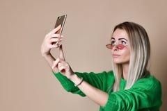 O retrato do close-up da mulher loura da forma alegre nova no desgaste da camiseta faz o selfie no smartphone, sobre o fundo bege imagem de stock royalty free