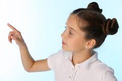 O retrato do close-up de uma menina bonita da criança olha ausente e aponta com seu dedo Fotos de Stock