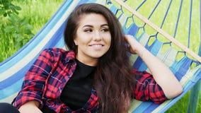 O retrato do close-up de uma menina feliz bonita encontra-se em uma rede no jardim, sorri-se e relaxa-se filme