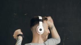 O retrato do close up do homem engraçado novo põe sobre fones de ouvido e a dança louca quando escute a música no fundo preto filme