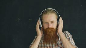 O retrato do close up do homem novo farpado nos fones de ouvido escuta a música e a vista no sorriso da câmera video estoque