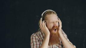 O retrato do close up do homem novo farpado põe sobre fones de ouvido e dança quando escute a música no fundo preto filme
