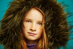 O retrato do close-up do estúdio da menina redheaded bonito da criança com sardas escondeu no grande revestimento da capa imagem de stock