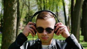 O retrato do close-up do estudante atrativo, homem põe sobre fones de ouvido que escuta a música video estoque