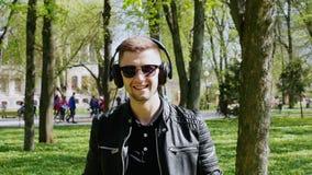 O retrato do close-up do homem atrativo põe sobre fones de ouvido e escuta a música filme