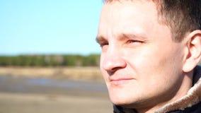O retrato do close up do movimento lento do homem novo do indivíduo que olha de sobrancelhas franzidas aprecia o sol exterior video estoque