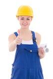 O retrato do construtor feliz da mulher em combinações azuis manuseia acima do isolador Imagem de Stock Royalty Free