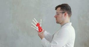 O retrato do coordenador do cientista conduz testes da mão protética robótico que tenta mover os dedos video estoque