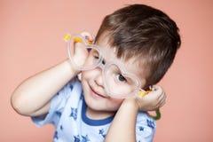 O retrato do coração vestindo do rapaz pequeno bonito deu forma a vidros fotografia de stock