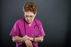 O retrato do doutor superior da senhora que guarda o pulso gosta de ferir fotografia de stock