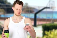 O retrato do esportes felizes equipa o campo de esporte próximo ereto com um telefone celular fora fotos de stock